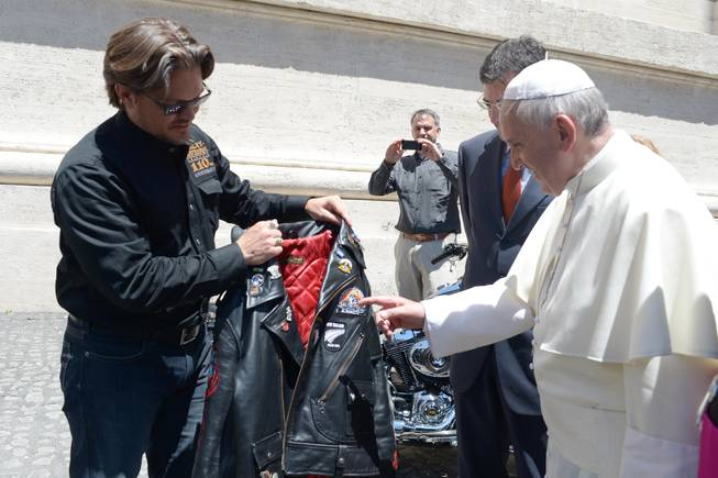 In this June 12, 2013, file photo provided by the Vatican paper L'Osservatore Romano, Pope Francis receives a leather jacket from Harley Davidson Motor Company senior vice-president Mark Hans-Richer, at the Vatican. A 1,585cc Harley-Davidson Dyna Super Glide, donated to Pope Francis last year and signed by him on its tank, will be sold at auction in Paris to help raise funds for a soup kitchen and hostel for the homeless in Rome.