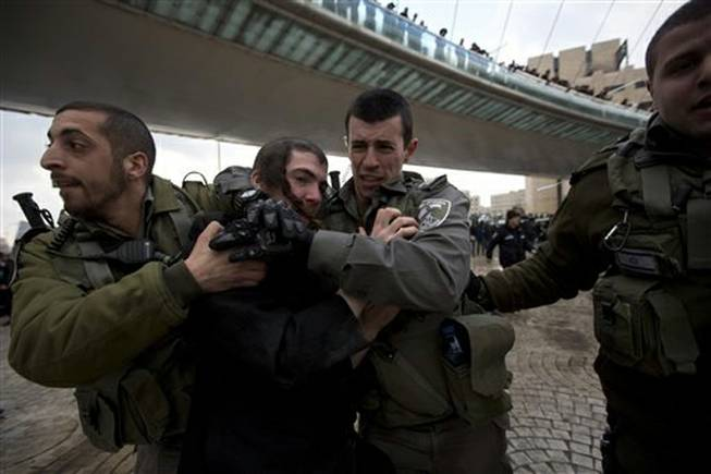Israeli border police officers detain an ultra-Orthodox Jewish man during a demonstration in Jerusalem, Thursday, Feb. 6, 2014. Israeli police said thousands of ultra-Orthodox Jews are blocking highways across the country to protest plans to enlist them into the military.
