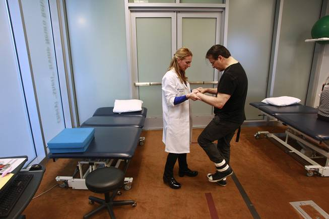 Physical therapist Jen Nash helps Kerry Simon walk across the room during a therapy session at the Cleveland Clinic Lou Ruvo Center for Brain Health on Feb. 7, 2014.