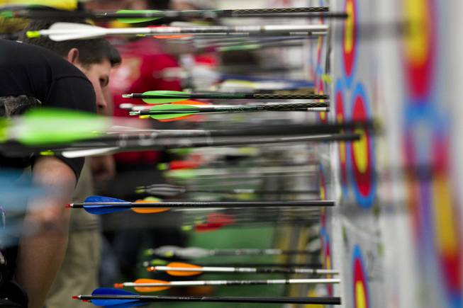 Archers verify points and retrieve their arrows during the Adult Freestyle Championship in the South Point Arena as part of the Vegas Round of the 2014 NFAA World Archery Festival on Friday, Feb. 7, 2014.
