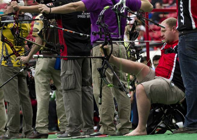 Archer Matt Stutzman of Fairfield, Iowa, holds his bow and releases arrows using only his feet on Friday, Feb. 7, 2014. He shot one of the top scores during the Adult Freestyle Championship in the South Point Arena in the Vegas Round of the 2014 NFAA World Archery Festival.