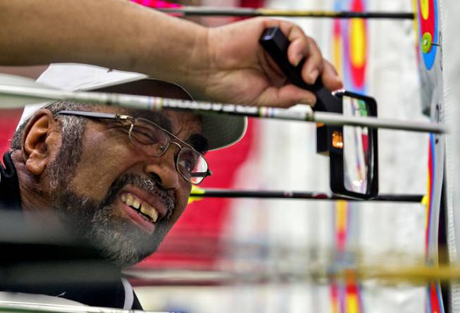 Tournament official Ron West of Capitol Heights, Maryland, uses a magnifying glass to score an arrow during the Adult Freestyle Championship in the South Point Arena as part of the Vegas Round of the 2014 NFAA World Archery Festival on Friday, Feb. 7, 2014.
