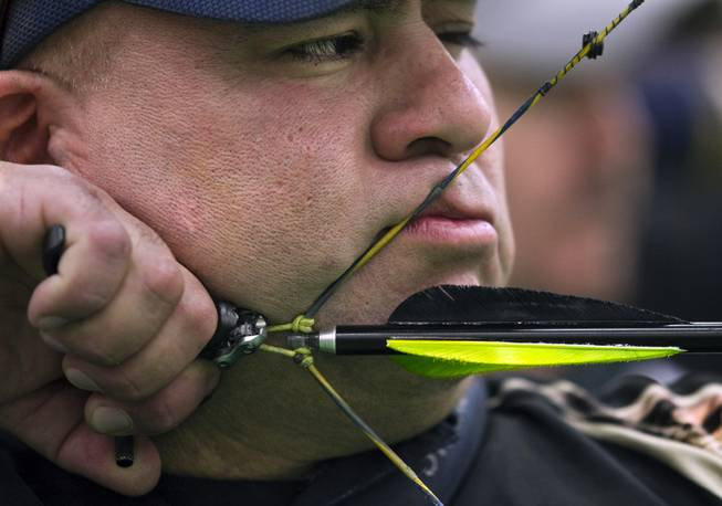 Archer Bernard Ortiz of Riverside, Calif., prepares to release another arrow snugged up to his face on Friday, Feb. 7, 2014. He shot one of the top scores during the Adult Freestyle Championship in the South Point Arena in the Vegas Round of the 2014 NFAA World Archery Festival.