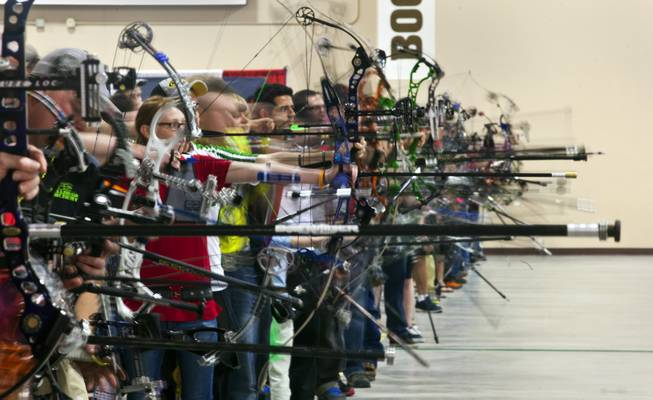 Competitors launch arrows in the practice area of the South Point Arena during the Vegas Round of the 2014 NFAA World Archery Festival on Friday, Feb. 7, 2014.