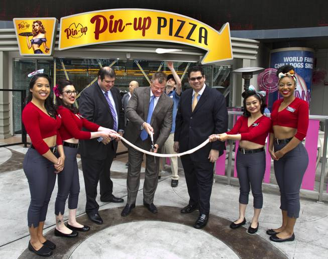 Planet Hollywood President David Hoenemeyer cuts the dough and is joined by Vice President of Food and Beverage Jeffrey Frederick, Director of Food and Beverage Terrence O'Donnell and Pin-Up Pizza girls at the grand opening Friday, Feb. 7, 2014, at Planet Hollywood.