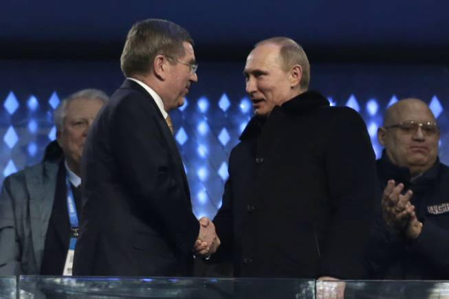 International Olympic Committee President Thomas Bach, left, shakes hands with Russian President Vladimir Putin during the opening ceremony of the 2014 Winter Olympics in Sochi, Russia, Friday, Feb. 7, 2014.