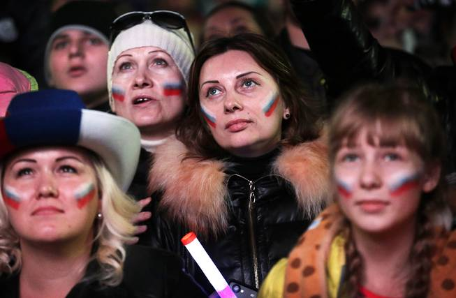 Russian women with their national flag painted on their cheeks watch intensely as the live telecast of the 2014 Winter Olympics opening ceremony is aired, Friday, Feb. 7, 2014, in downtown Sochi, Russia.