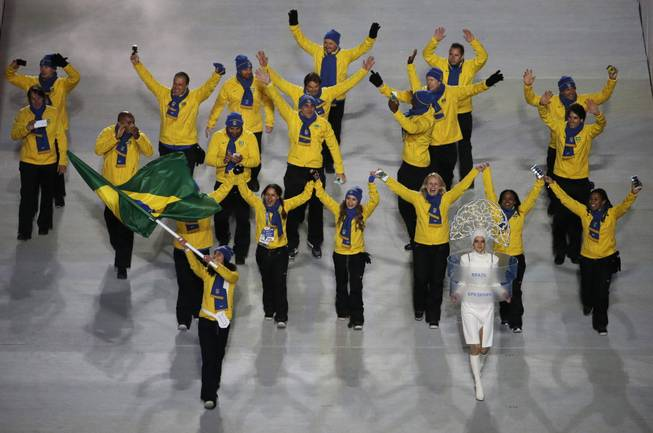 Jaqueline Mourao of Brazil waves her national flag and enters the arena with her team during the opening ceremony of the 2014 Winter Olympics in Sochi, Russia, Friday, Feb. 7, 2014.