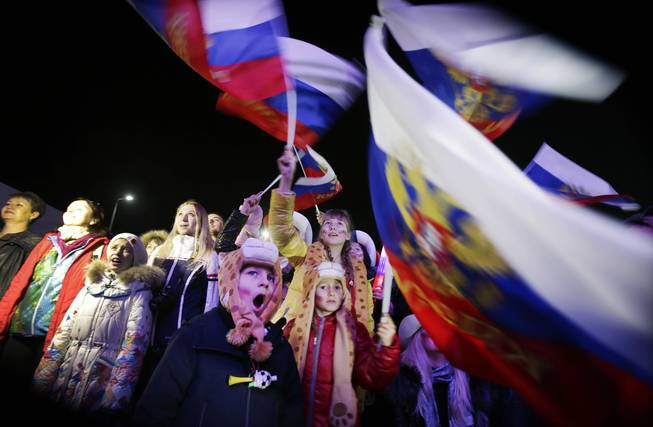 A Russian child yawns while others wave the national flag as the Russian national anthem is played during the live telecast of the 2014 Winter Olympics opening ceremony, Friday, Feb. 7, 2014, in downtown Sochi, Russia.