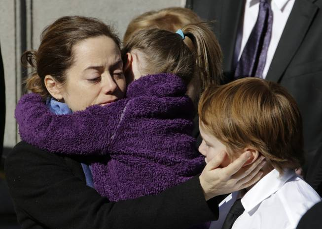 Mimi O'Donnell, estranged partner of actor Philip Seymour Hoffman, comforts two of their children, daughter Willa, and son Cooper as his casket arrives at the Church of St. Ignatius Loyola, Friday, Feb. 7, 2014 in New York. Hoffman, 46, was found dead Sunday of an apparent heroin overdose.