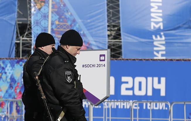 Russian Special Rapid Response Unit personnel patrol the parameters of the Olympic cauldron, ahead of the 2014 Winter Olympics opening ceremony, Friday, Feb. 7, 2014, in Sochi, Russia.