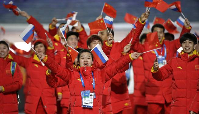 Members of the Chinese team wave Russian and Chinese flags as they arrive during the opening ceremony of the 2014 Winter Olympics in Sochi, Russia, Friday, Feb. 7, 2014.