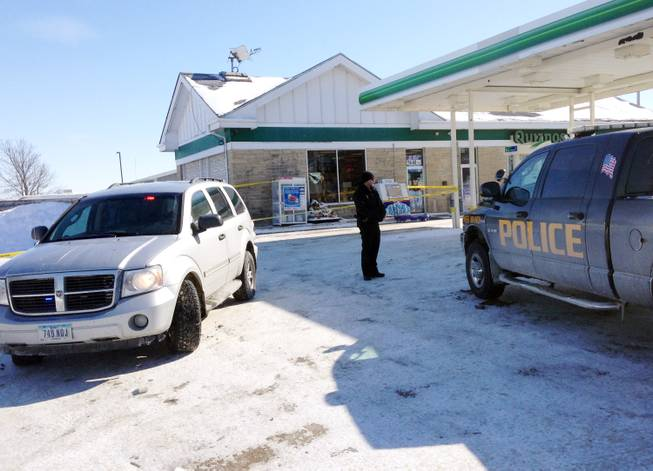 Authorities gather at a gas station in West Branch, Iowa, where a missing newborn was found alive Friday, Feb. 7, 2014. Police said they found Kayden Powell, who's nearly a week old, after they heard the newborn crying and found the child swaddled in blankets inside a tote bag outside the gas station. Police said the baby was in excellent health.