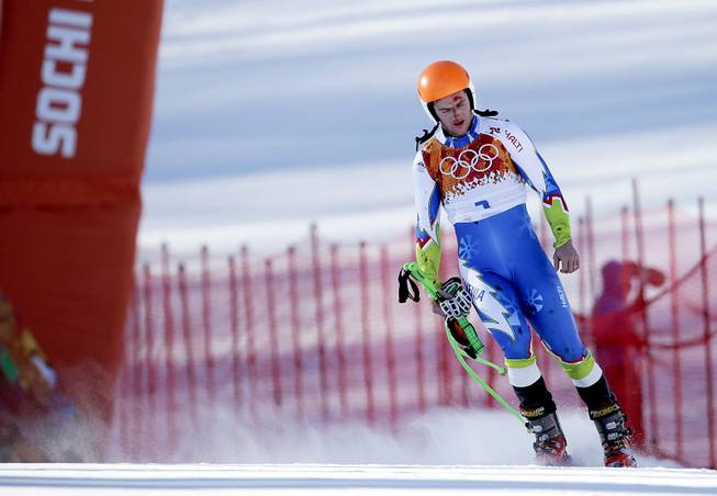 Slovenia's Rok Perko arrives in the finish area after crashing during a men's downhill training run for the Sochi 2014 Winter Olympics, Saturday, Feb. 8, 2014, in Krasnaya Polyana, Russia.