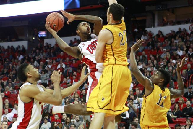 UNLV forward Roscoe Smith is defended by Wyoming forward Larry Nance Jr. as he drives to the basket during their game Saturday, Feb. 8, 2014 at the Thomas & Mack Center. UNLV won 48-46.