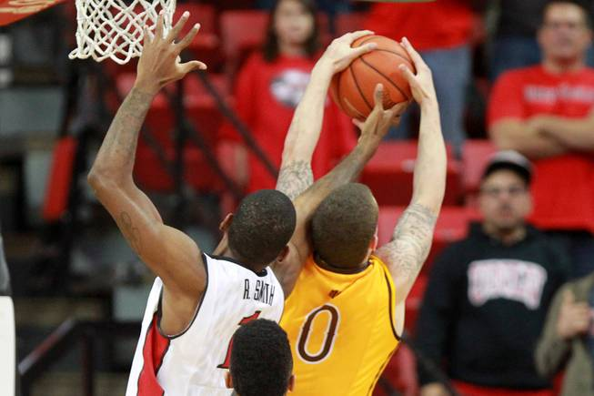 UNLV forward Rosco Smith knocks a rebound away from  Wyoming guard Josh Smith during the final seconds of their game Saturday, Feb. 8, 2014 at the Thomas & Mack Center. UNLV won 48-46.