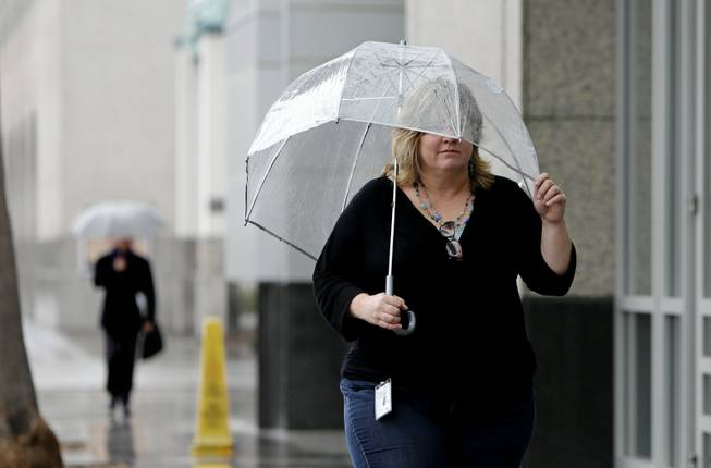 Molly Emslie found the need for an umbrella as showers swept through Sacramento, Calif., on Friday, Feb. 7, 2014. Drought-stricken California is getting some relief as a storm system the likes of which, forecasters say, the region has not seen in more than a year.