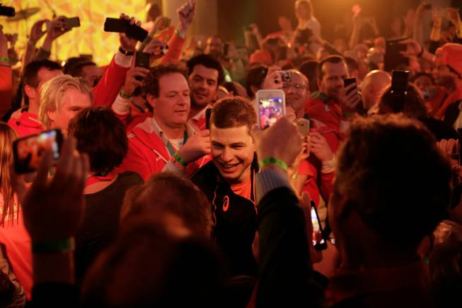 Under orange lighting, gold medallist Sven Kramer of the Netherlands walks through a crowd of cheering fans after winning the gold in the men's 5,000-meter speedskating race at the 2014 Winter Olympics in Sochi, Russia, on Saturday, Feb. 8, 2014. Kramer set a new Olympic record in the race.