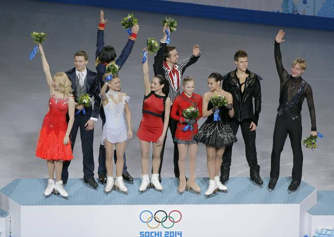 The Russian team waves to spectators from the podium during the flower ceremony after placing first in the team figure skating competition at the Iceberg Skating Palace during the 2014 Winter Olympics, Sunday, Feb. 9, 2014, in Sochi, Russia.