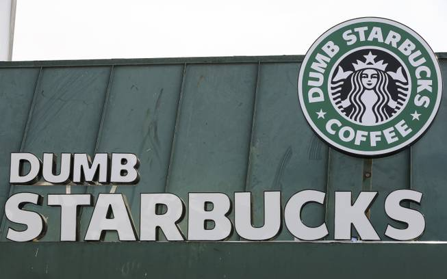 "The sign at Dumb Starbucks coffee in Los Angeles is displayed Monday, Feb. 10, 2014. The store resembles a Starbucks with a green awning and mermaid logo, but with the word ""Dumb"" attached above the Starbucks sign. Starbucks spokeswoman Laurel Harper says the store is not affiliated with Starbucks and, despite the humor, the store cannot use the Starbucks name."