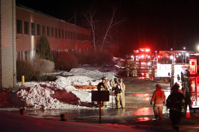 Emergency crews from several towns work an area outside the New Hampshire Ball Bearing plant after an explosion, Monday, Feb. 10, 2014, in Peterborough, N.H.