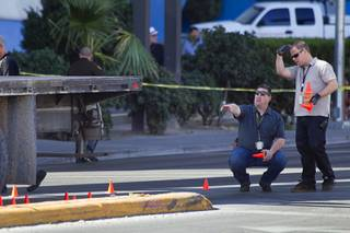 Metro Police investigators look over the scene of an auto pedestrian accident at Flamingo Road and Linq Lane (between Koval Lane and the Las Vegas Strip) Tuesday Feb. 11, 2014.