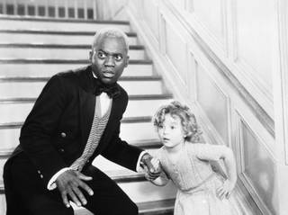 Bill Robinson as the butler is caught in the act of teaching Shirley Temple his world famous stair dance in a scene from