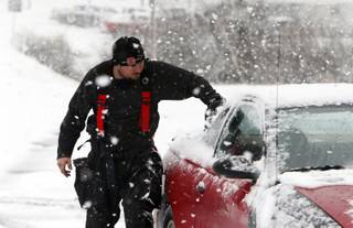 Firefighter Robbie Hairell scrapes snow off of his car Tuesday Feb. 11,  2014 in Dog Town, Ala.  A winter storm dropped from 1 inch to 3 inches of wintry precipitation across a wide area, turning trees and roads white and forcing hundreds of schools, businesses and government offices to close or open late.  (AP Photo/Hal Yeager)