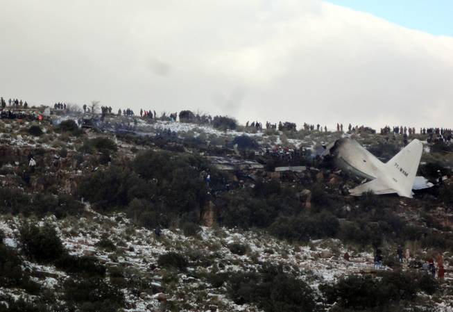 People look at the wreckage of Algerian military transport plane after it slammed into a mountain in the country's rugged eastern region, Tuesday, Feb. 11, 2014.