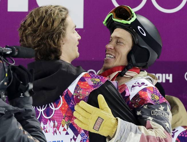Switzerland's Iouri Podladtchikov, left, celebrates with Shaun White of the United States after Podladtchikov won the gold medal in the men's snowboard halfpipe final at the Rosa Khutor Extreme Park, at the 2014 Winter Olympics, Tuesday, Feb. 11, 2014, in Krasnaya Polyana, Russia.
