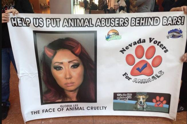 "Protesters with Nevada Voters for Animals hold a banner declaring Gloria Lee as ""the face of animal cruelty."" Lee is accused of setting her Las Vegas pet shop on fire on Jan. 27. The protesters are turning out for court hearings in  Lee's case to send a message to the judge that they want the harshest treatment possible for Lee."