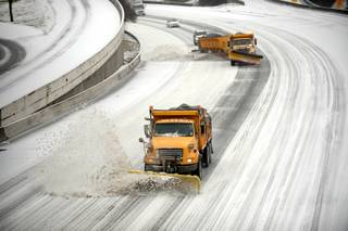 Snow plows clear downtown lanes on Interstate 75/85 during a winter storm on Wednesday, Feb. 12, 2014, in Atlanta.  Across the South, winter-weary residents woke up Wednesday to a region encased in ice, snow and freezing rain, with forecasters warning that the worst of the potentially