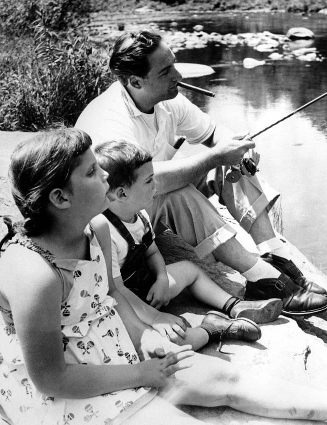 Comedian Sid Caesar relaxes with fishing rod while his children, Shelly, 6, and Ricky, 27 months, sit beside him during their vacation in Upstate New York in June 1954.