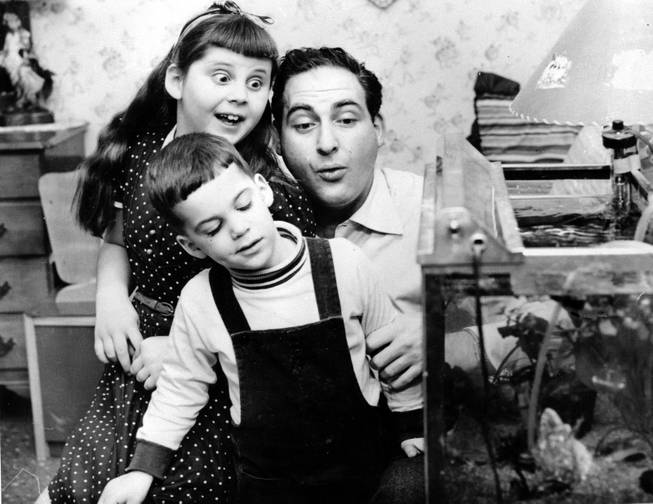 Comedian Sid Caesar is shown at home with his daughter Shelley, 8, and son Richard, 3, on May 25, 1955 at Kings Point, Long Island, N.Y.