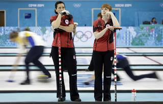 Canada's Jill Officer, left, and Dawn McEwen, right, wait on the sidelines of the ice sheet during the women's curling competition against Britain at the 2014 Winter Olympics, Wednesday, Feb. 12, 2014, in Sochi, Russia.
