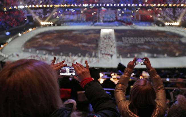 A spectator takes a video of the opening ceremony on her mobile phone at the 2014 Winter Olympics in Sochi, Russia, Friday, Feb. 7, 2014.
