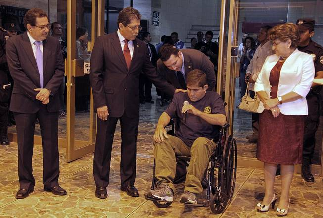 Jose Salvador Alvarenga holds a microphone intending to speak, after arriving at the airport in San Salvador, El Salvador, Tuesday, Feb. 11, 2014. Alvarenga was wheeled in a wheelchair before a crush of more than 100 mostly foreign journalists. But when handed the microphone, he held it in silence.