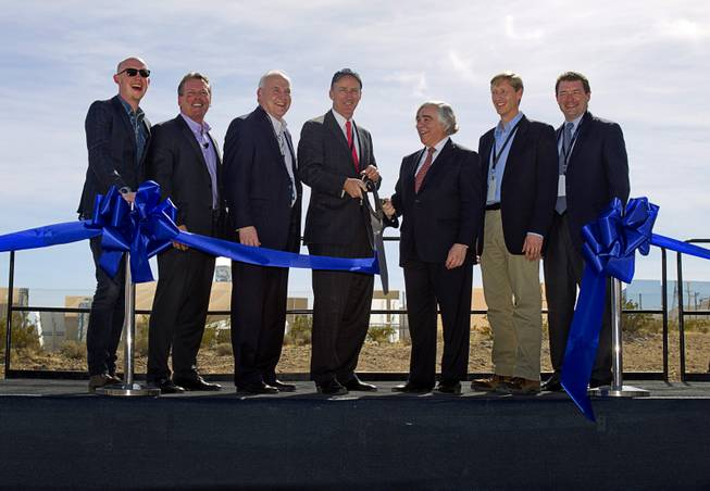 Officials cut a ceremonial ribbon during the grand opening of the Ivanpah Solar Electric Generating System in the Mojave Desert in California near Primm, Nev. Feb. 13, 2014. The project, a partnership of NRG, BrightSource, Google and Bechtel, is the world's largest solar thermal facility. From left are: Isaac Slade, lead singer of The Fray, Tom Doyle, president/CEO of NRG Solar, David Ramm, CEO of BrightSource Energy, David Crane, president/CEO of NRG Energy, United States Secretary of Energy Ernest Moniz, Rick Needham, Google's director of sustainability and energy, and Toby Seay, president of Bechtel Power.