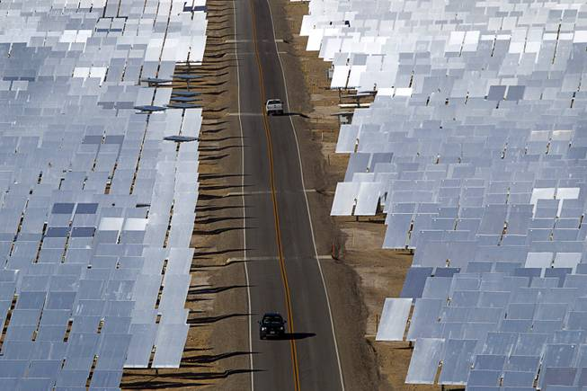 Vehicles drive through field of heliostats (mirrors that track the sun and reflect the sunlight onto a central receiving point) at the Ivanpah Solar Electric Generating System in the Mojave Desert in California near Primm, Nev. Feb. 13, 2014. The project, a partnership of NRG, BrightSource, Google and Bechtel, is the world's largest solar thermal facility and uses 347,000 sun-facing mirrors to produce 392 megawatts of electricity, enough energy to power more than 140,000 homes.