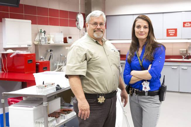 Clark County Coroner Investigators Rick Jones and Felicia Borla stand inside the autopsy room at the Clark County Coroner's Office Thursday, Feb. 13, 2014.