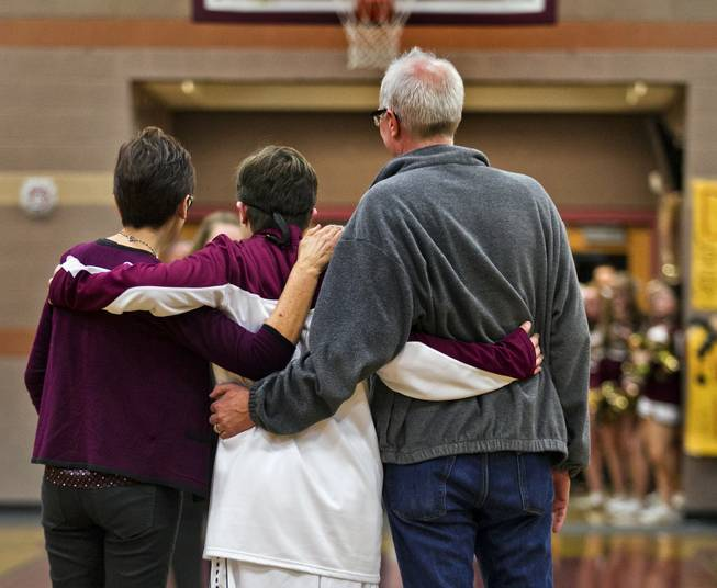 "Shelley, Clayton and John Rhodes walk onto the court as they participate in ""senior night"" link arms as they are photographed before the start of the varsity basketball game against Pahrump on Thursday, Feb. 13, 2014."