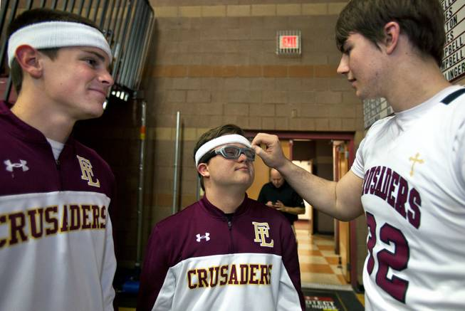 Faith Lutheran senior Clayton Rhodes has a new sweatband adjusted by teammate John Molchon as they prepare on the court for their varsity basketball game against Pahrump on Thursday, Feb. 13, 2014.