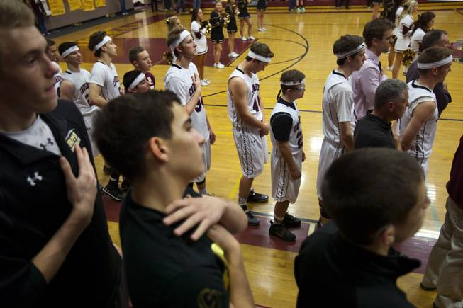 "Faith Lutheran varsity basketball players, coaches and fans stand and face the flag for the singing of the ""Star Spangled Banner"" before the start of their game against Pahrump on Thursday, Feb. 13, 2014."