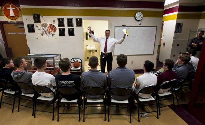 Faith Lutheran High School's CEO Dr. Steve Buuck gives the devotional to varsity basketball players before the start of their game against Pahrump on Thursday, Feb. 13, 2014.