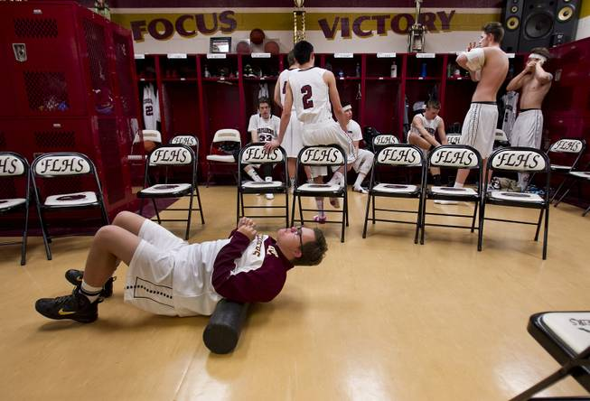 Faith Lutheran senior Clayton Rhodes stretches out as he and varsity basketball teammates ready in their locker room before the start of their game against Pahrump on Thursday, Feb. 13, 2014.
