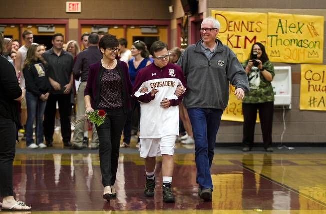 "Shelley, Clayton and John Rhodes walk onto the court as they participate in ""senior night"" recognitions before the start of the varsity basketball game against Pahrump on Thursday, Feb. 13, 2014."