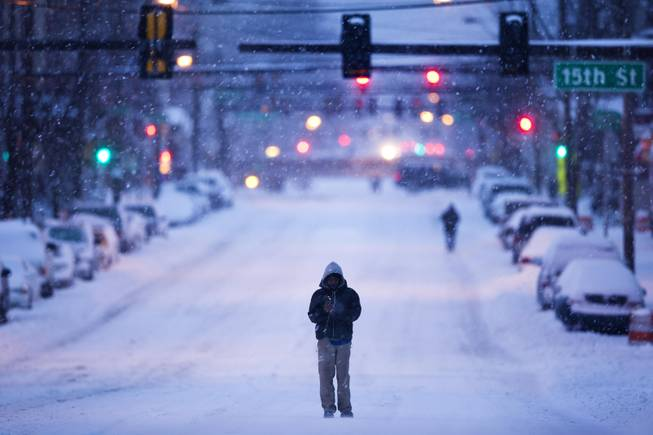 A morning commuter walks in the plowed road as mixed winter precipitation falls Thursday, Feb. 13, 2014, in Philadelphia. Snow and sleet are falling on the East Coast, from North Carolina to New England, a day after sleet, snow and ice bombarded the Southeast. (AP Photo/Matt Rourke)