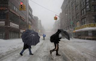 Pedestrians use umbrellas as they walk through falling snow in the Chinatown neighborhood of New York, Thursday, Feb. 13, 2014. Snow and sleet are falling on the East Coast from North Carolina to New England a day after sleet, snow and ice bombarded the Southeast.