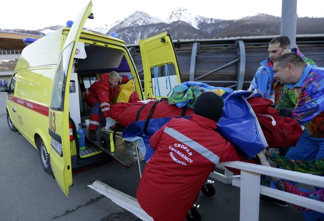 A track worker is loaded into an ambulance after he was injured when a forerunner bobsled hit him just before the start of the men's two-man bobsled training at the 2014 Winter Olympics, Thursday, Feb. 13, 2014, in Krasnaya Polyana, Russia.