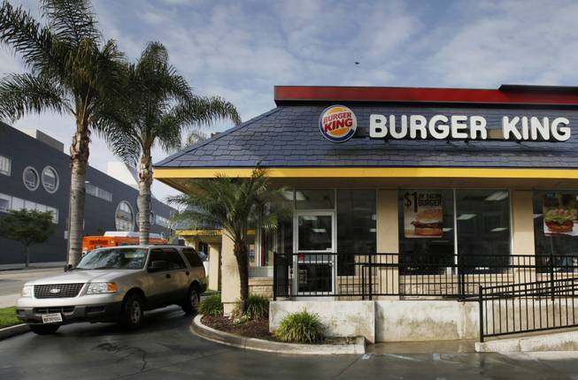 In this Thursday, April 25, 2013, file photo, a car stops at the drive-thru at a Burger King restaurant near downtown Los Angeles.
